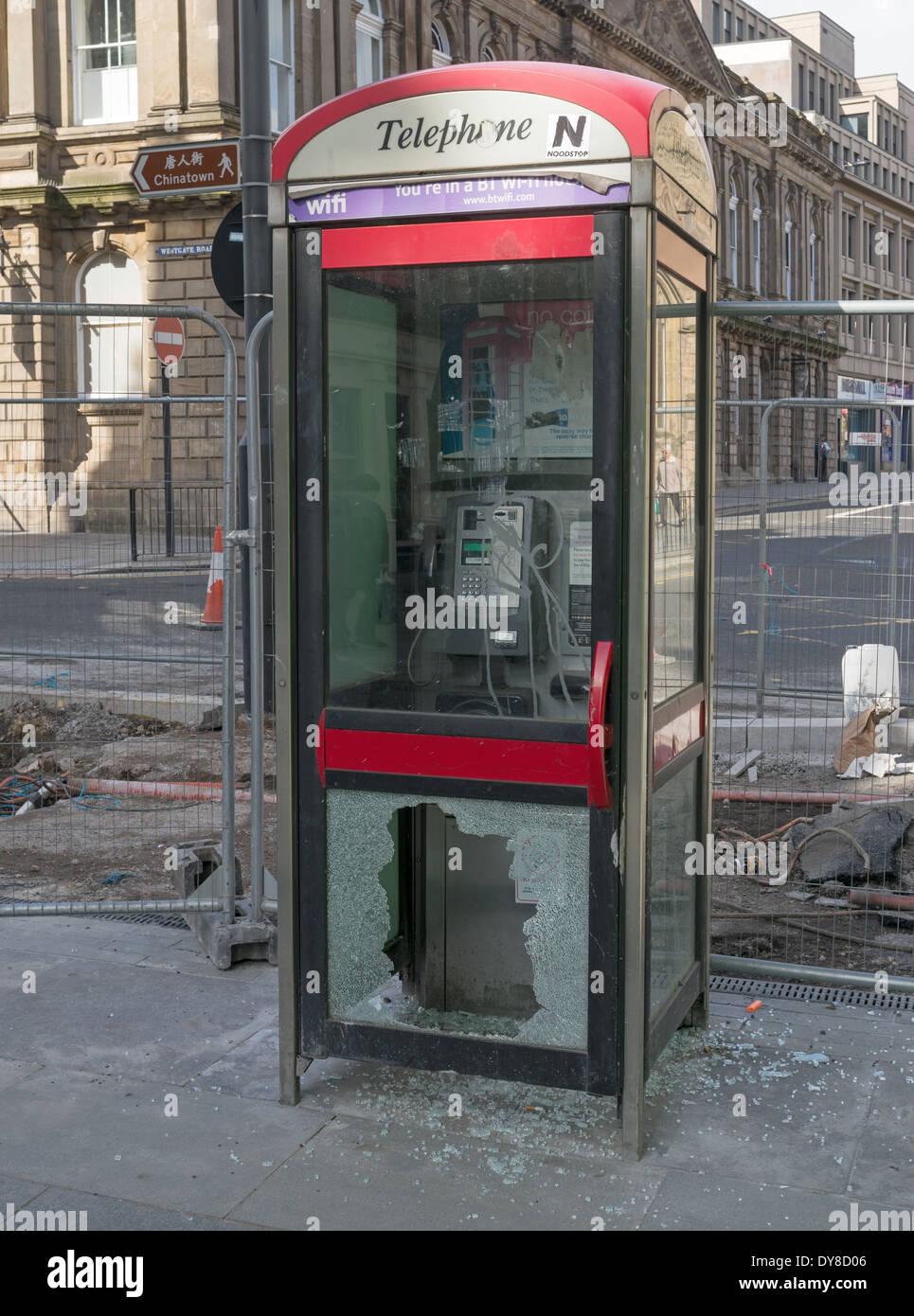 Vandalised telephone box or kiosk with broken glass door Newcastle north east England UK - Stock Image
