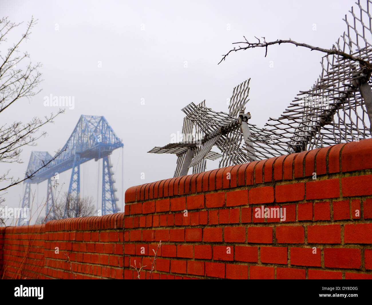 Historic Transporter Bridge spanning the River Tees, behind brick wall at Middlehaven, Middlesbrough, Teesside, England, UK - Stock Image