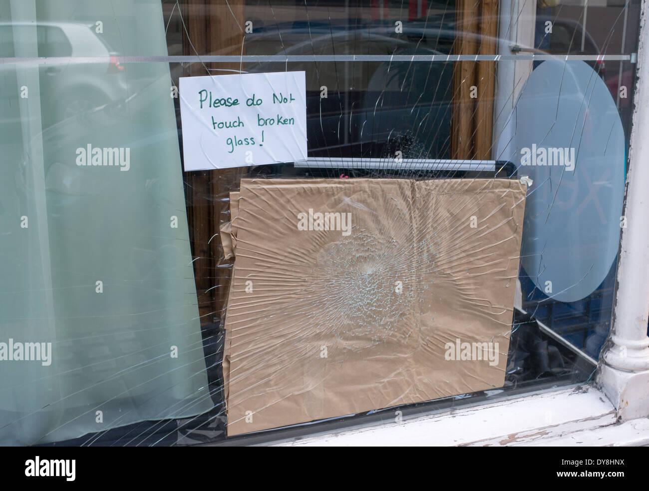 Vandalism, a shop window broken within Newcastle, north east England UK - Stock Image