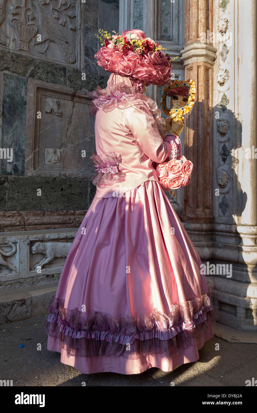 Lady in long elegant pink costume and mask standing looking into a mirror at the Venice carnival Stock Photo