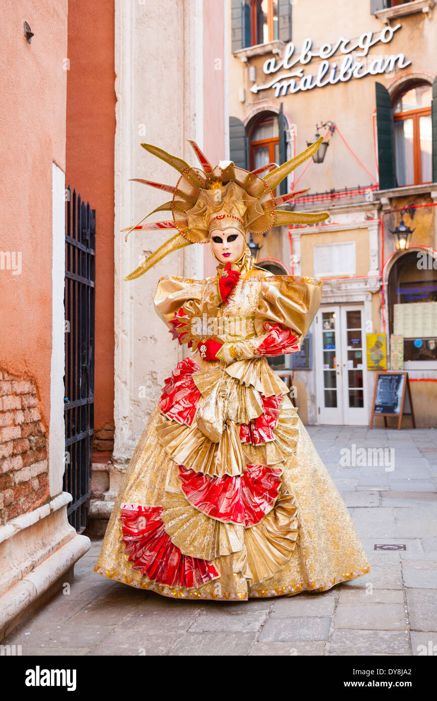Masked woman in golden ball gown costume posing during the carnival in Venice Stock Photo
