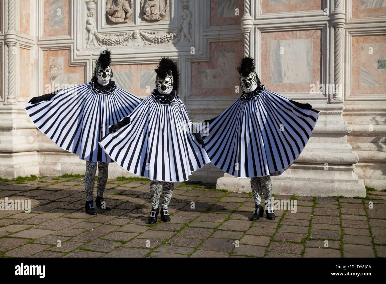Three masked participants in zebra costumes posing at a church during the Venice carnival & Three masked participants in zebra costumes posing at a church ...