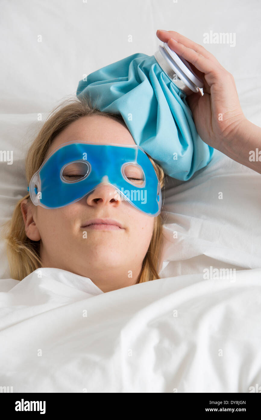 Young woman has a hangover, his eyes cooled with a cooling mask Stock Photo