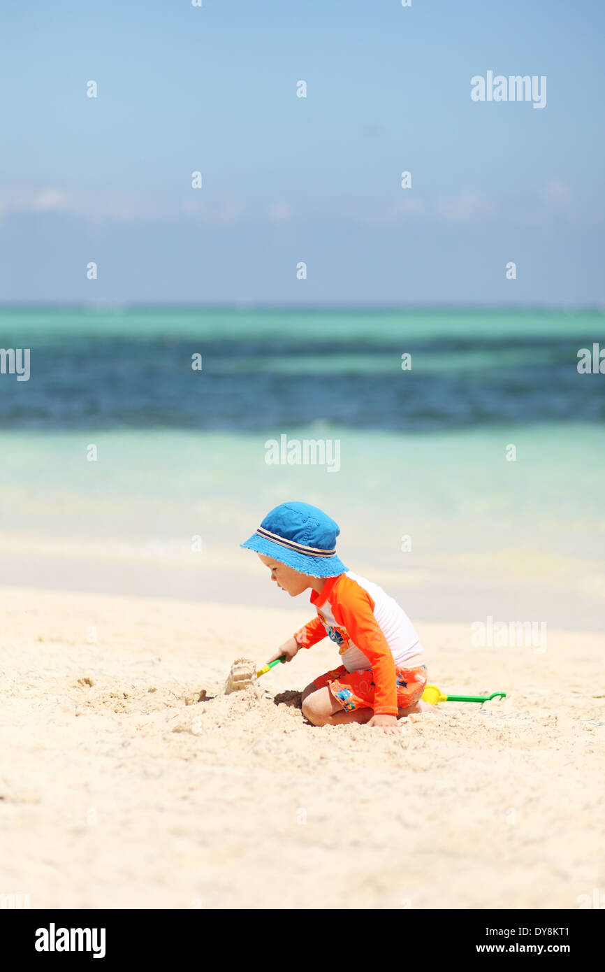 One caucasian boy playing with sand at tropical beach - Stock Image