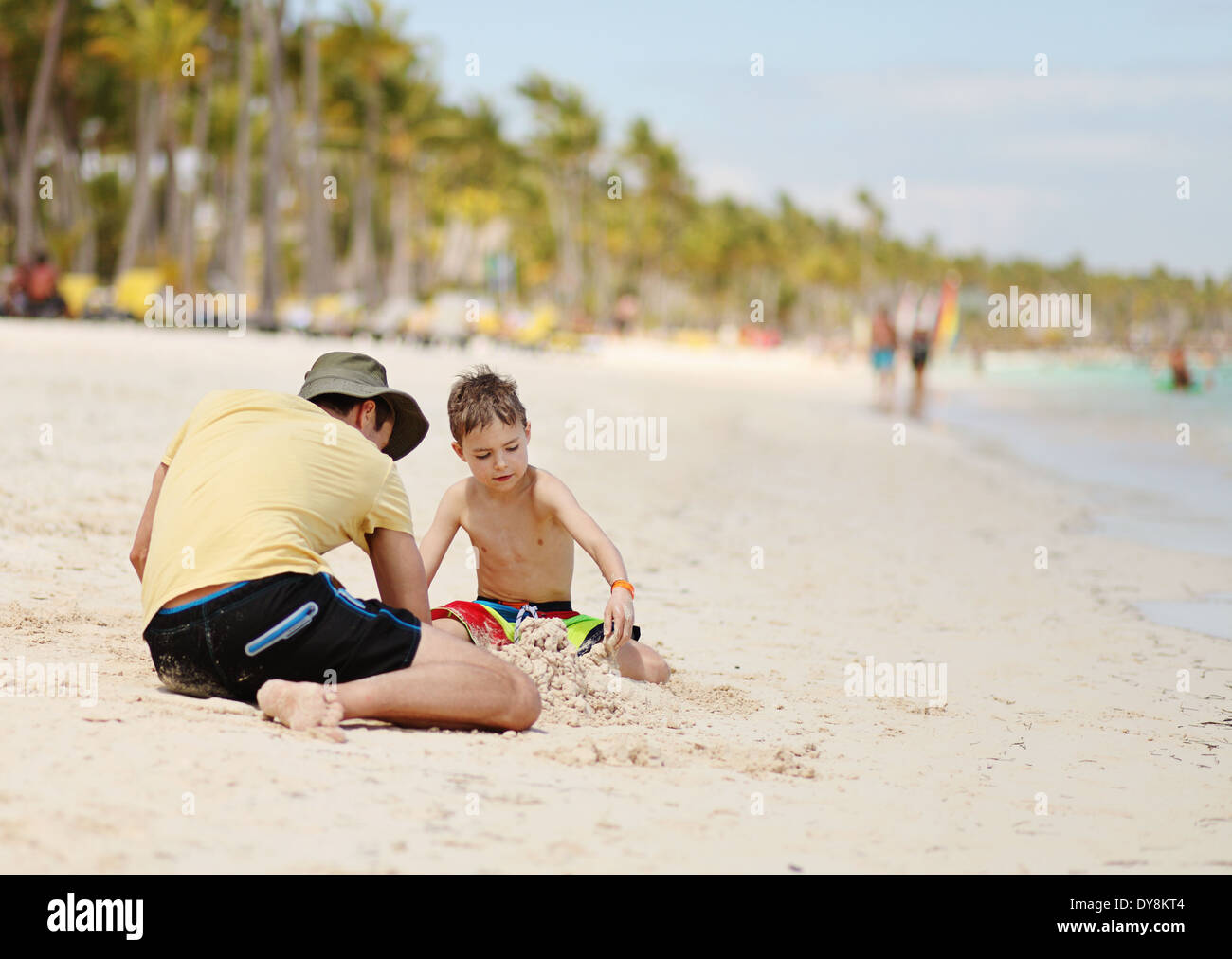 Caucasian boy and father playing with sand at tropical beach - Stock Image