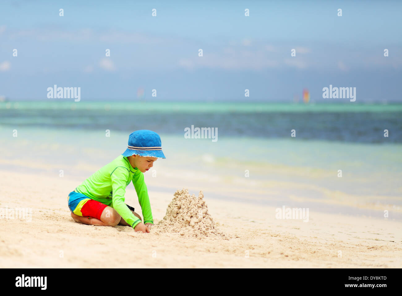 Caucasian boy building sand castle on tropical beach - Stock Image