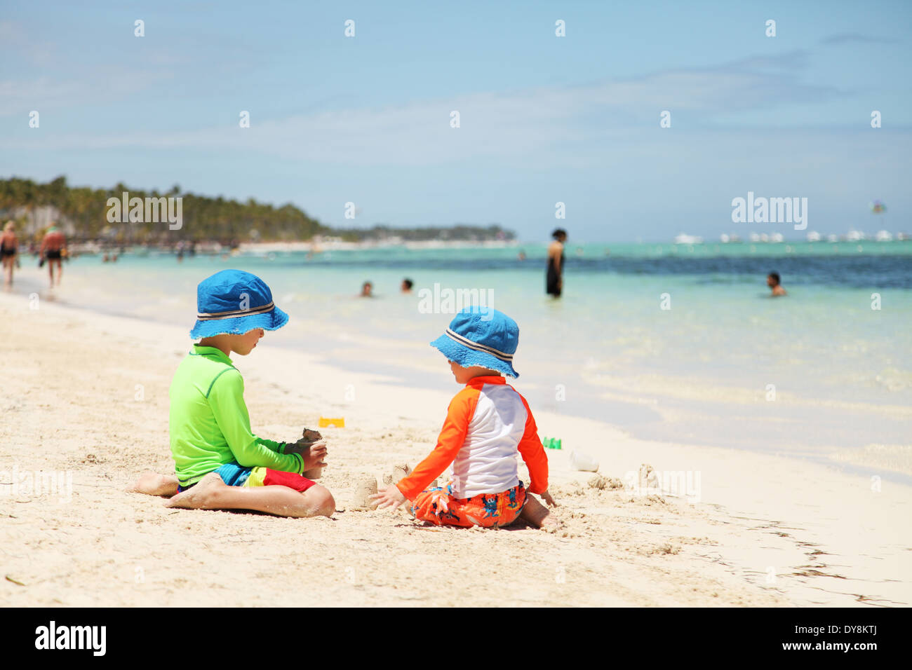 Two caucasian boys playing with sand at tropical beach - Stock Image
