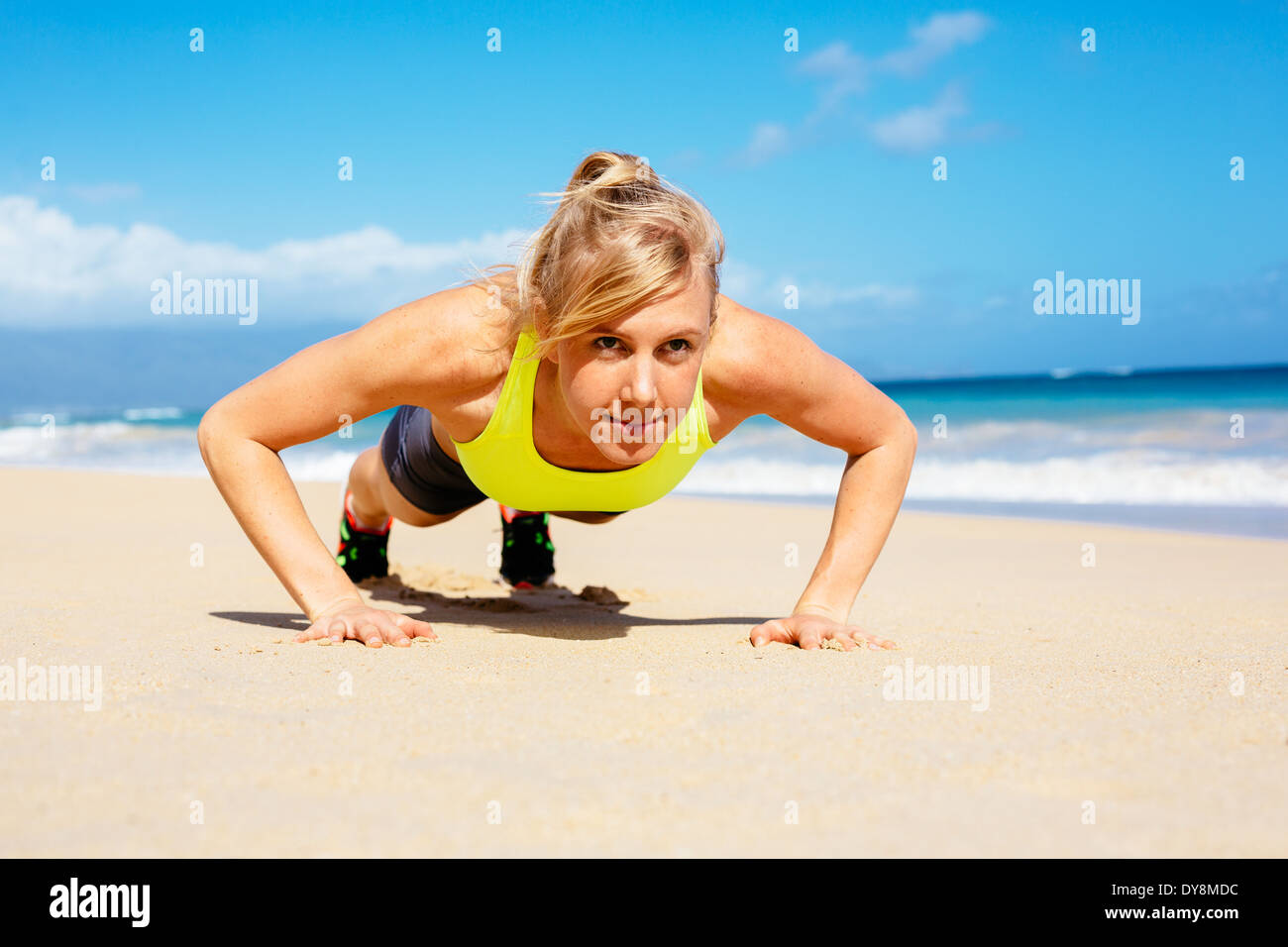 Young attractive woman doing push ups outside. Fitness woman working out at the beach. Crossfit exercise. - Stock Image