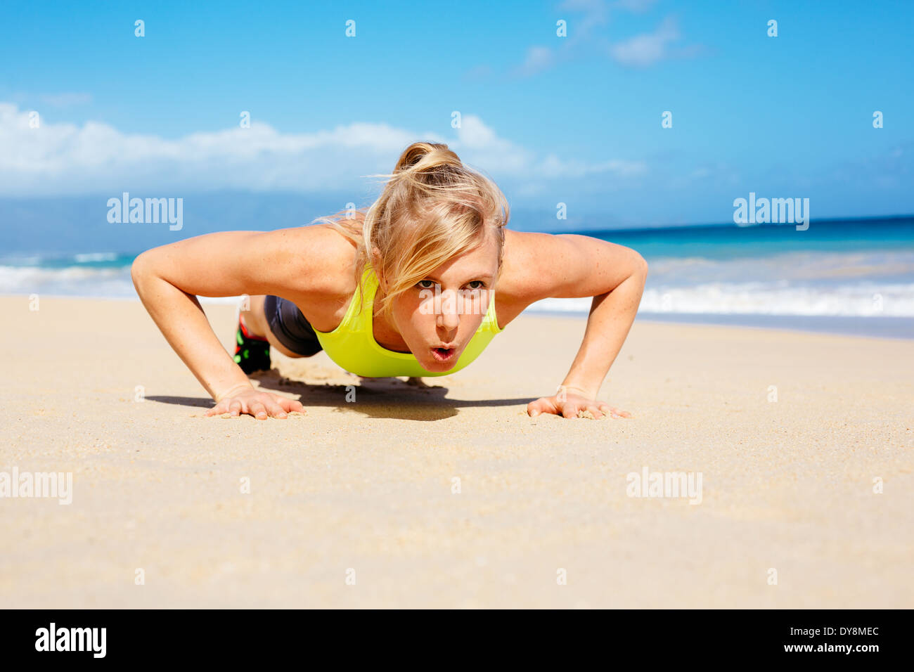 Young attractive woman doing push ups outside. Fitness woman working out at the beach. Crossfit exercise. Fitness Concept. - Stock Image