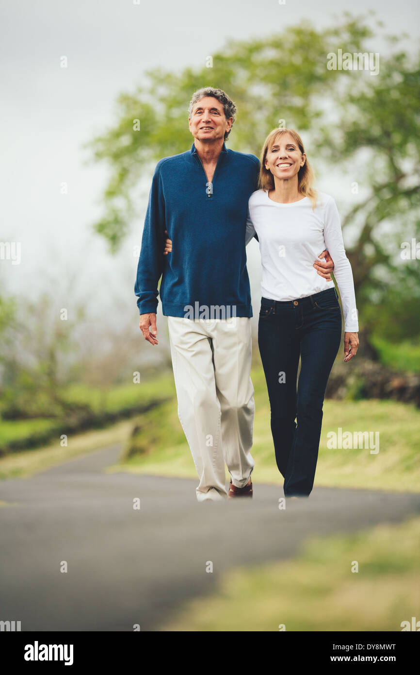Happy loving middle aged couple walking on beautiful country road - Stock Image