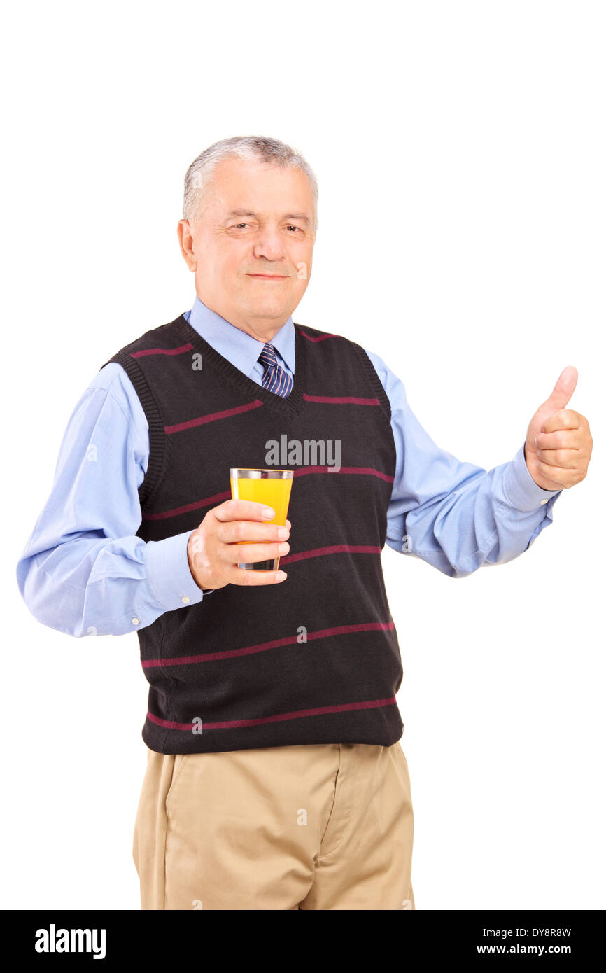 Mature man holding an orange juice and giving thumb up - Stock Image
