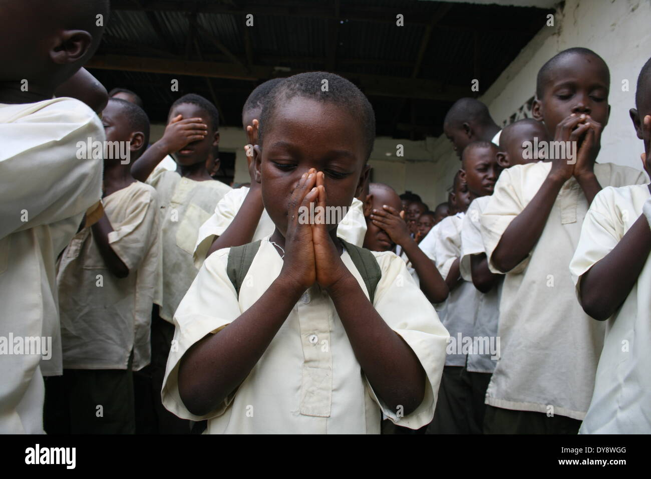 Young Kelvin Harris prays with his school mates. He was given the nickname 'Didier Drogba' by his father because of his impressi - Stock Image