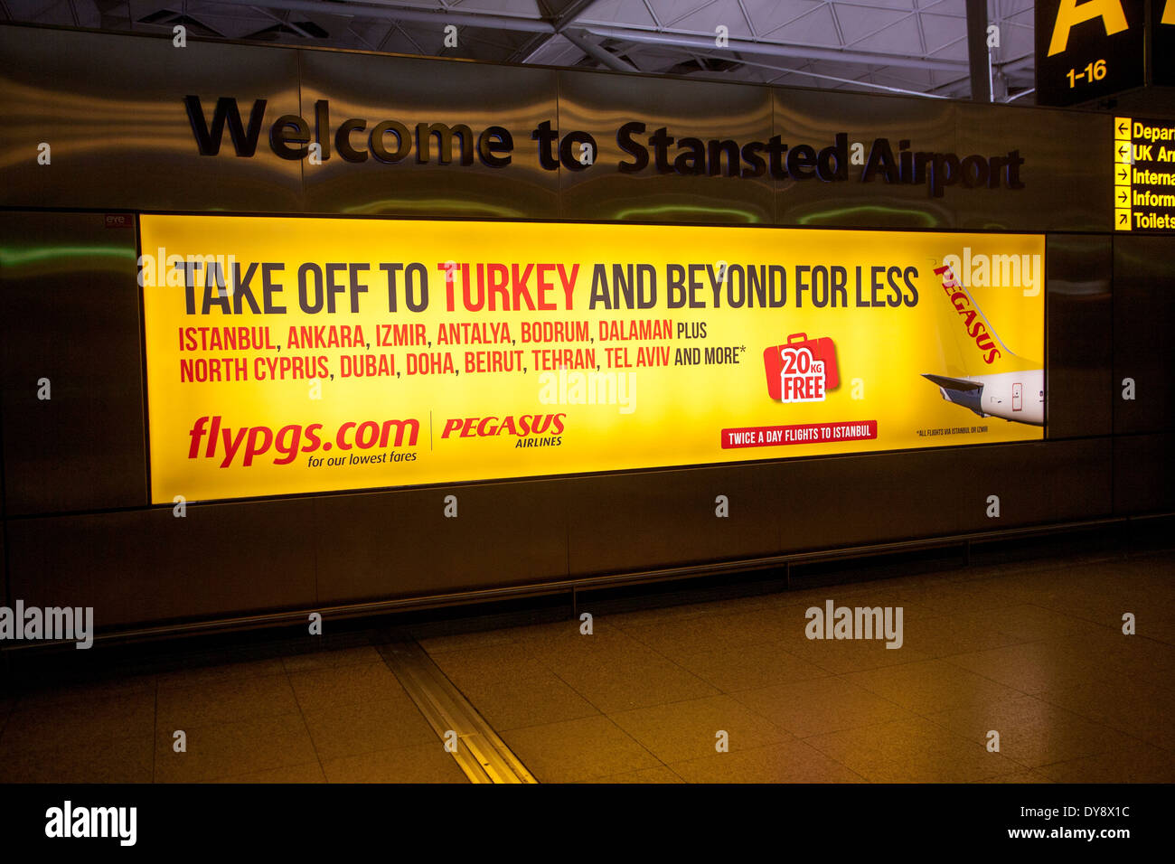 Electronic display advertising for Pegasus airlines flights to Turkey, Stansted airport, Essex, England - Stock Image