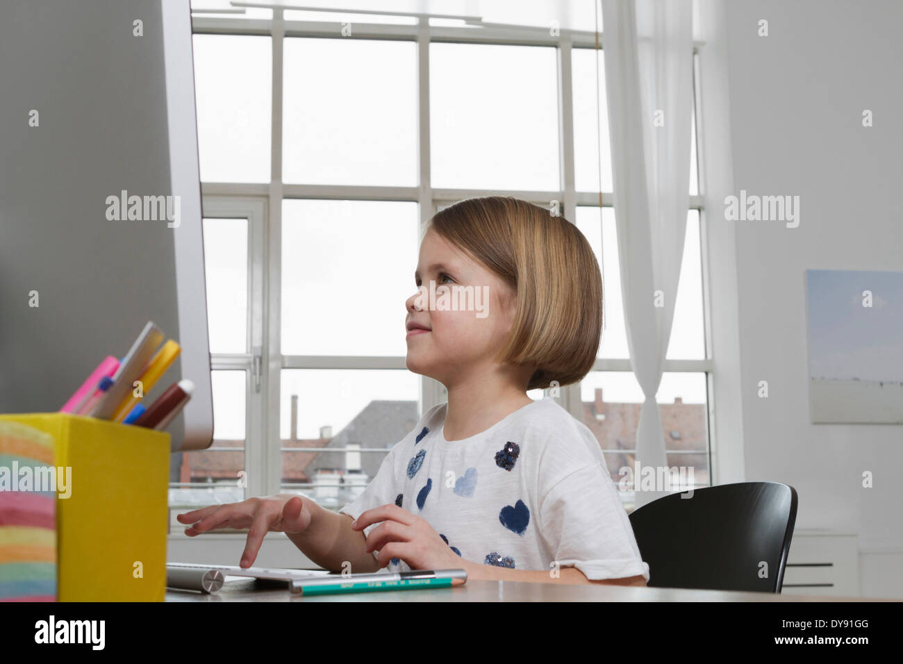 Girl at desk using computer keyboard - Stock Image