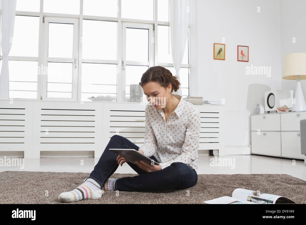 Woman at home using tablet computer - Stock Image