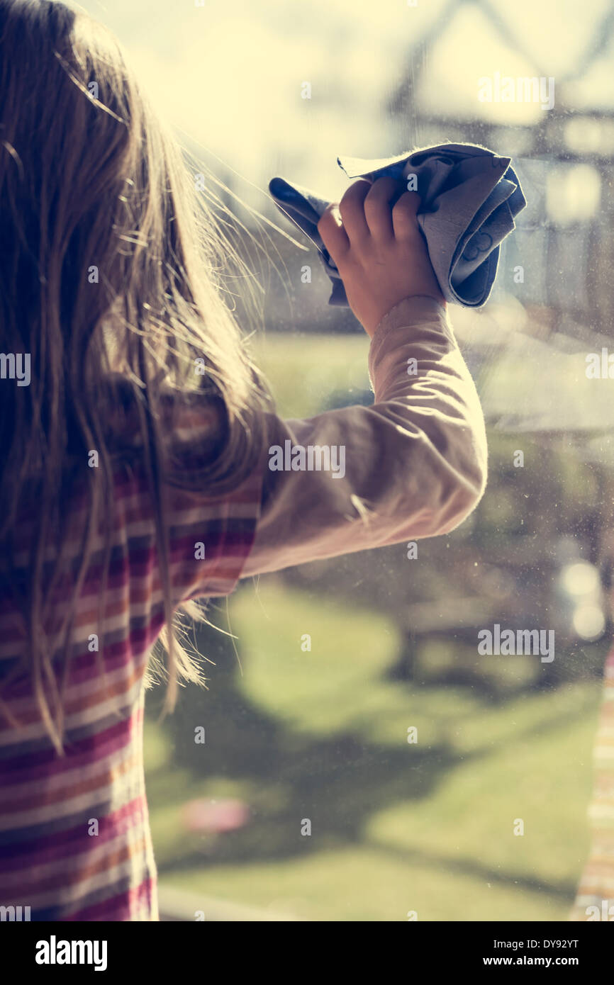 Little girl cleaning window - Stock Image