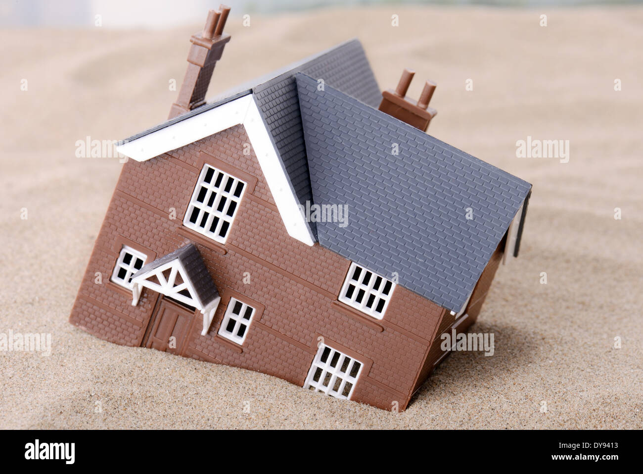 A house sinking in sand, concept for housing problems - Stock Image
