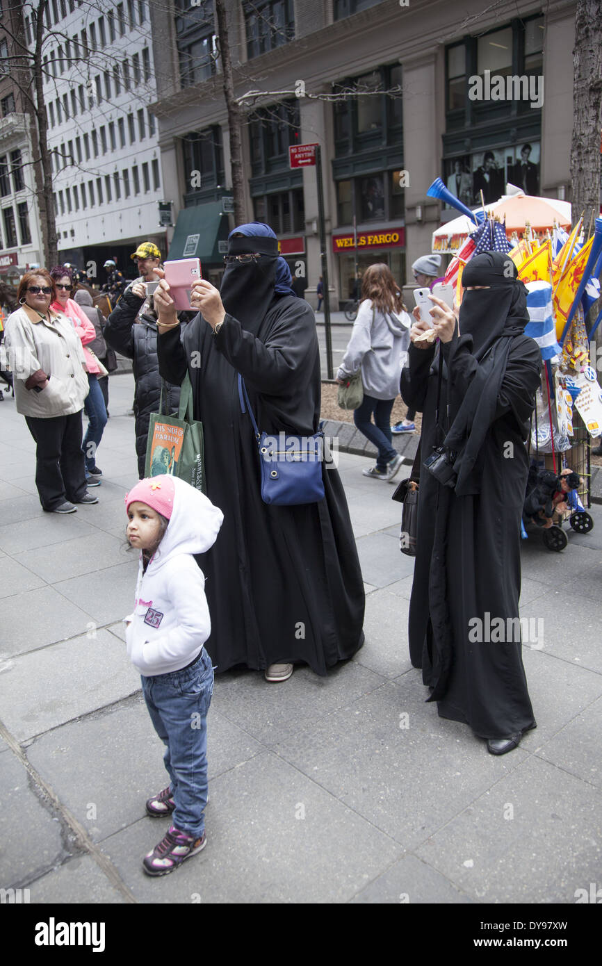Completely covered Muslim women in Burkas snap photos at the Tartan Day Parade in NYC. - Stock Image