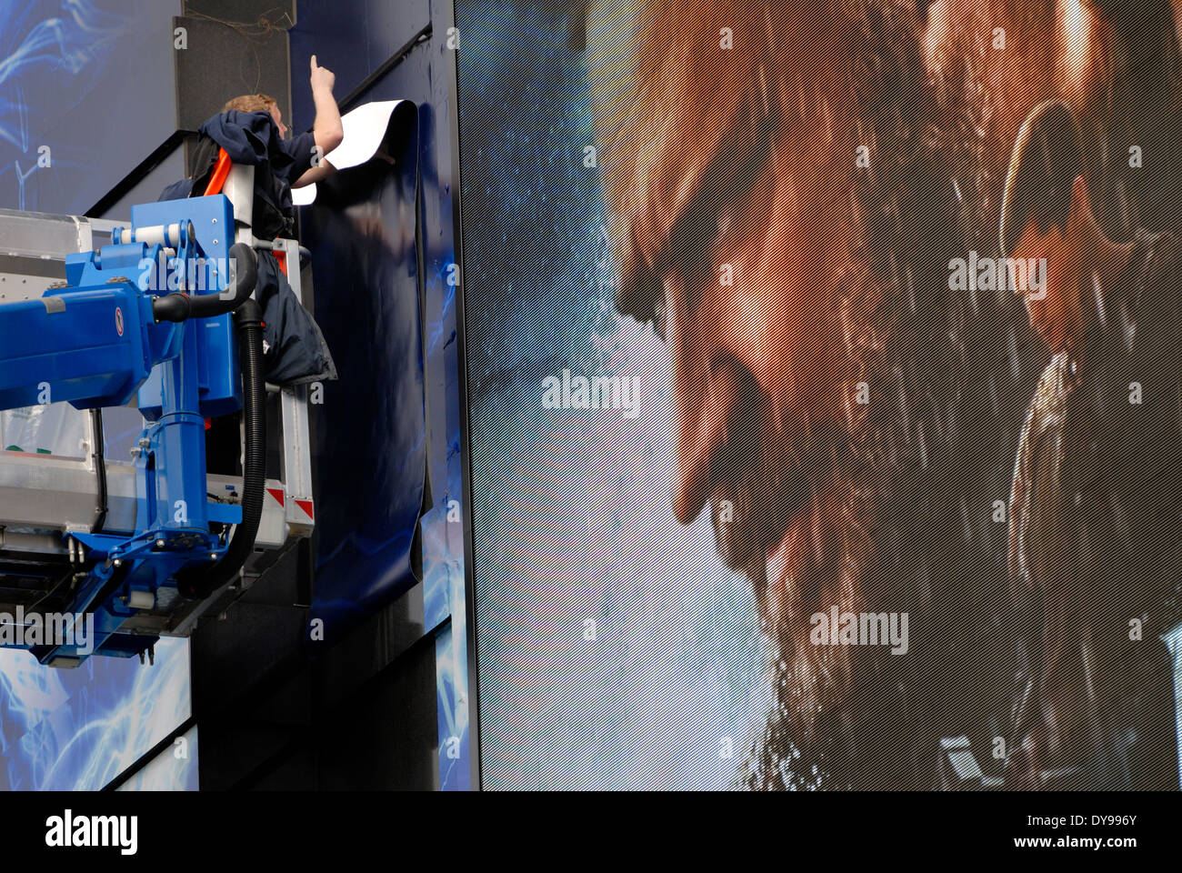 London, England, UK. Odeon Cinema, Leicester Square. Men sticking posters to facade for Noah film (2014) - Stock Image
