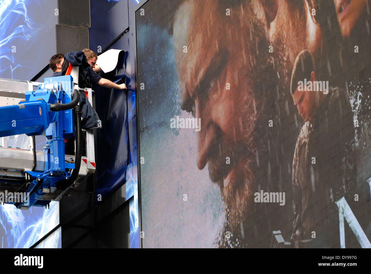 London, England, UK. Odeon Cinema, Leicester Square. Men sticking posters to facade for Noah film, 2014. - Stock Image