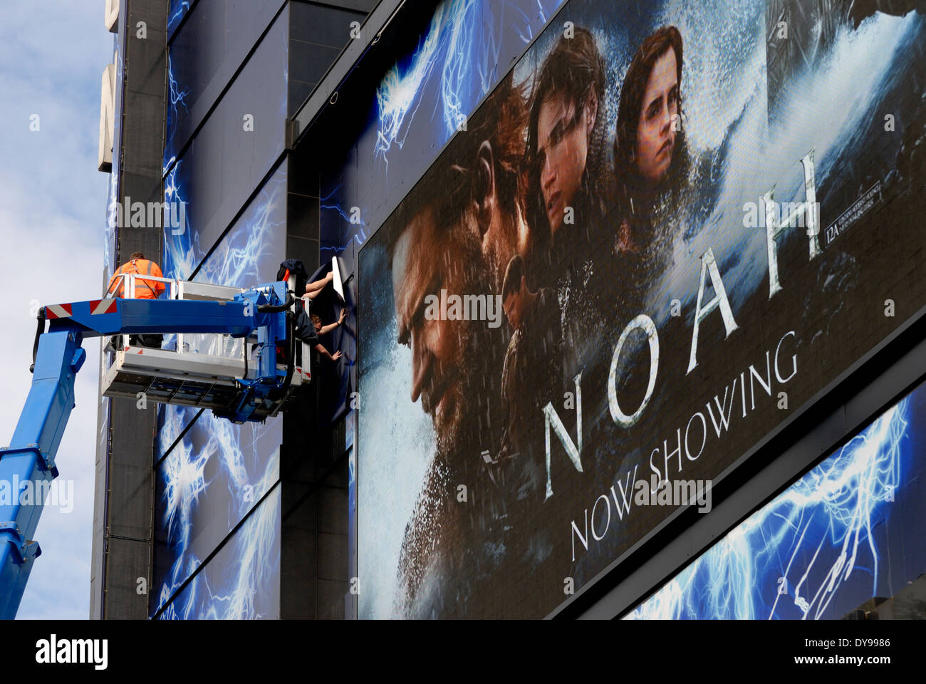 London, England, UK. Odeon Cinema, Leicester Square. Men sticking posters to facade for Noah film, 2014 - Stock Image