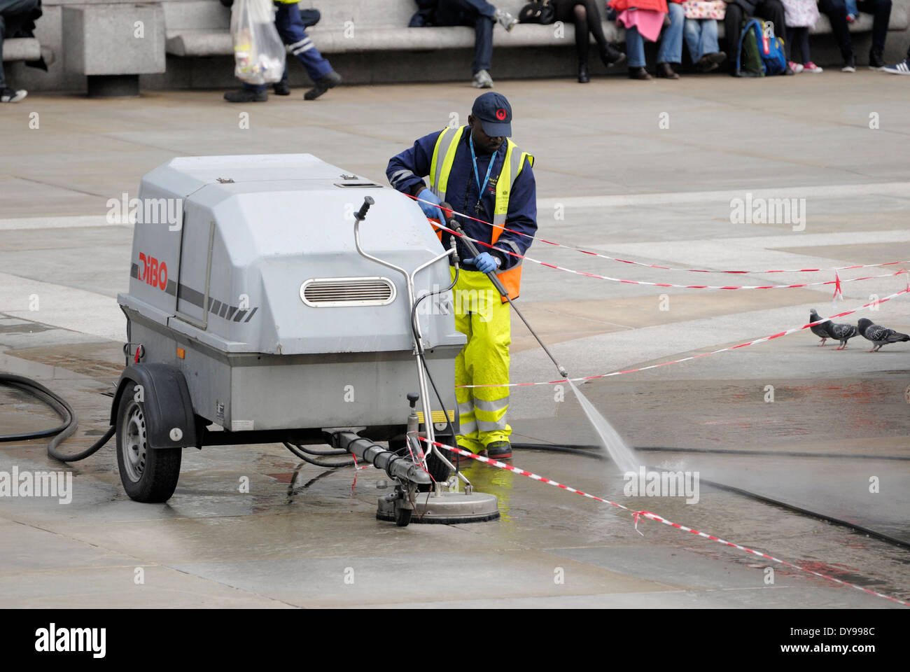 London, England, UK. Worker cleaning Trafalgar Square with high pressure water hose - Stock Image