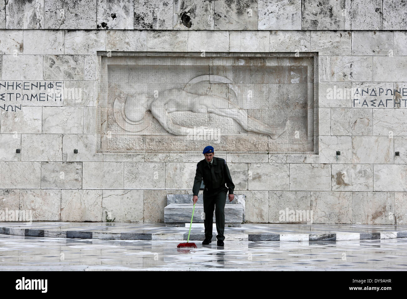Athens, Greece. 10th Apr, 2014. A Greek soldier wipes the rainwater in front of the monument of the Unknown Soldier in Syntagma Square. Evzones perform the Changing of the Guard Ceremony at the Tomb of the Unknown Soldier in Syntagma Square in Athens, Greece on April 10, 2014. Credit:  Konstantinos Tsakalidis/Alamy Live News - Stock Image