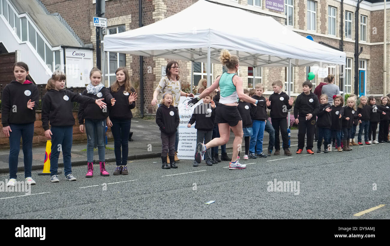 2014 ASICS Manchester Marathon - The runners reach the half away stage in the market town of Altrincham in Cheshire. - Stock Image