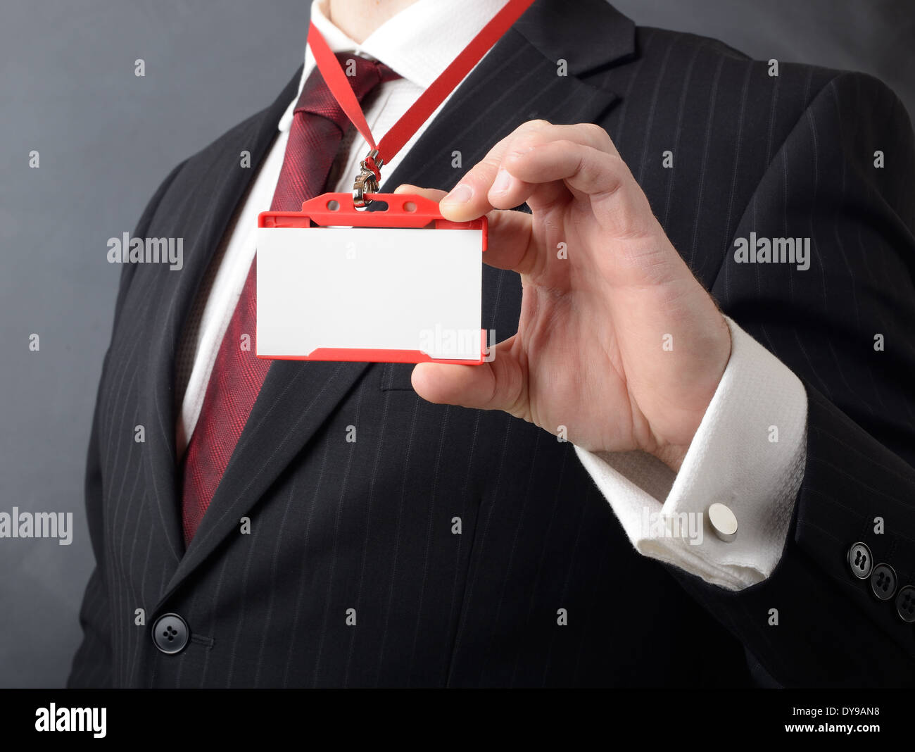 man in suit showing id or name badge - Stock Image