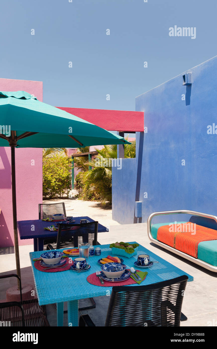 Breakfast area in comtemporary courtyard with brighly coloured walls - Stock Image
