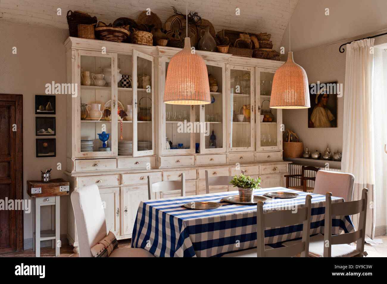 Rustic country kitchen with French style cabinets, checked blue tablecloth and woven wicker pendant lights - Stock Image