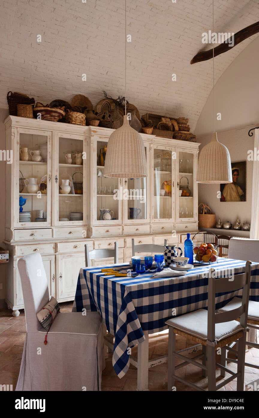 Rustic Country Kitchen With French Style Cabinets, Checked Blue Tablecloth  And Woven Wicker Pendant Lights