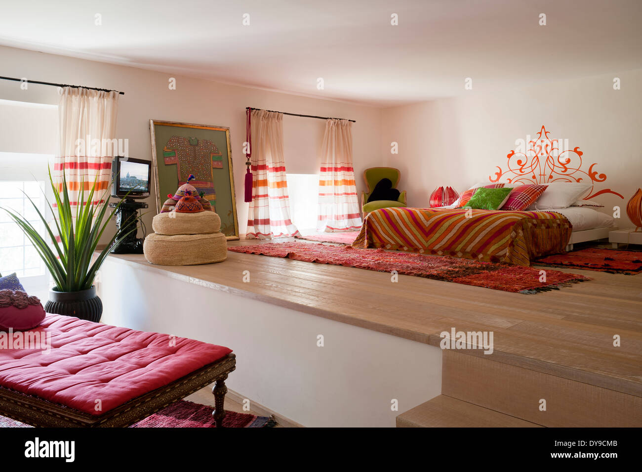 Warm Indian And Moroccan Inspired Bedroom With Brightly Coloured Fabrics  And Limed Oak Floors