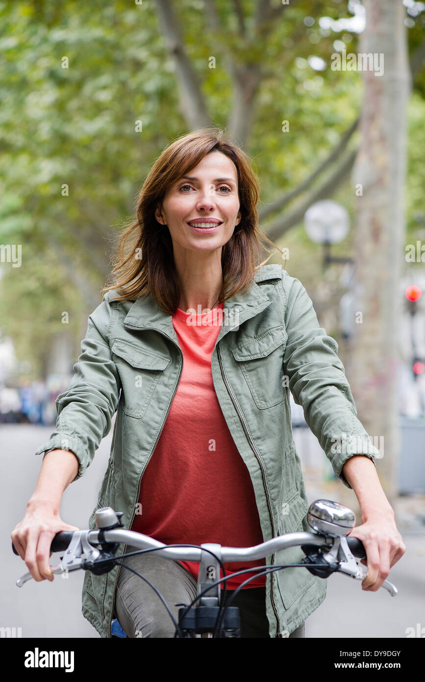 Woman riding bicycle in city - Stock Image