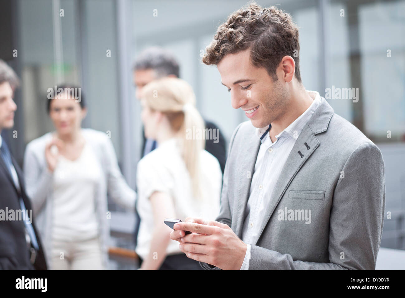 Businessman using cell phone while on the move - Stock Image