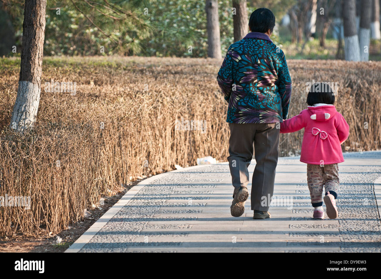 Woman with her granddaughter walking in small park in Beijing, China - Stock Image