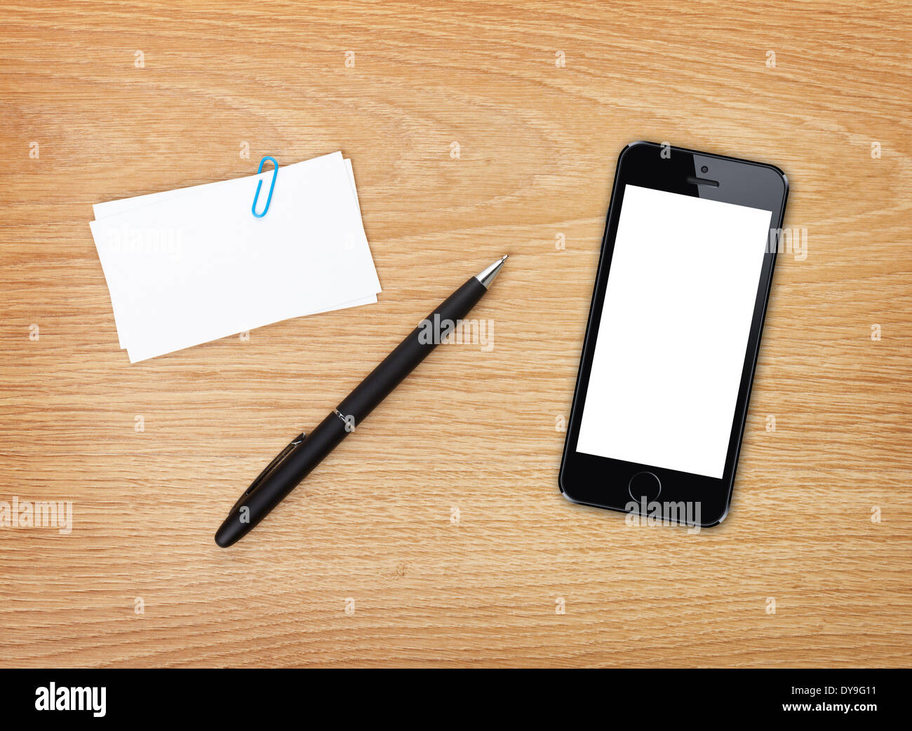 Business cards, pen and mobile phone on office table. Above view ...