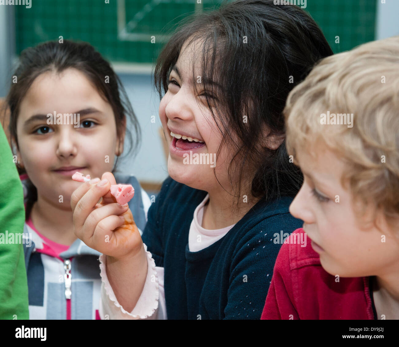 Non-disabled and disabled pupils (in this case a girl suffering from Down's syndrome) learn together in the same classroom. - Stock Image