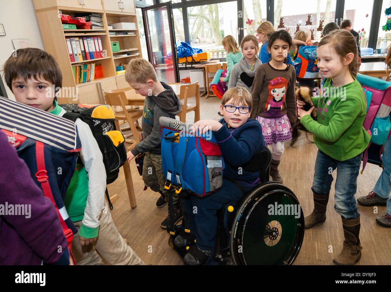 Non-disabled and disabled students (in this case a boy in a wheel chair) learn together in the same class in a primary school. - Stock Image