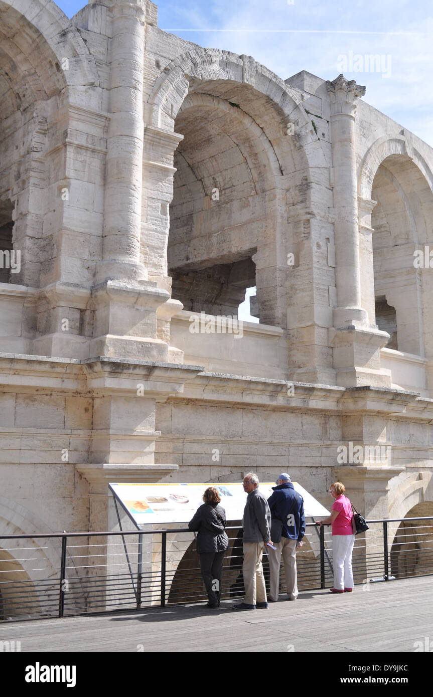 Tourists visit the spruced-up stone-blasted arches of the Roman Amphitheatre in Arles France - Stock Image