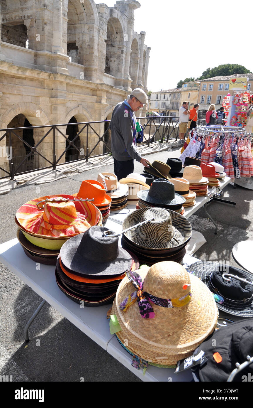 Man looks at hats on stall in front of the spruced-up stone-blasted arches of the Roman Amphitheatre in Arles France - Stock Image