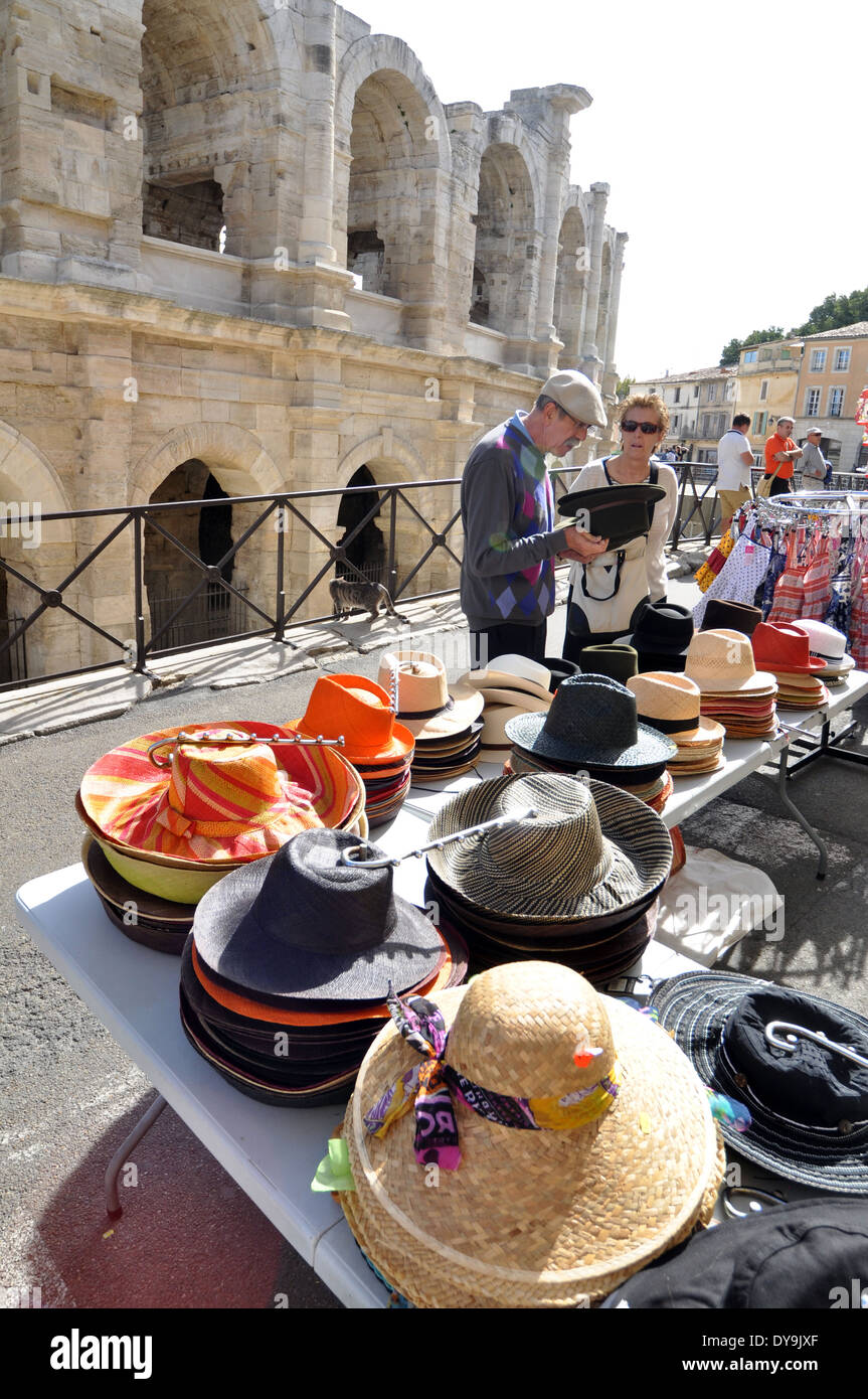 Man and woman look at hats on stall in front of the spruced-up stone-blasted arches of the Roman Amphitheatre in Arles France - Stock Image