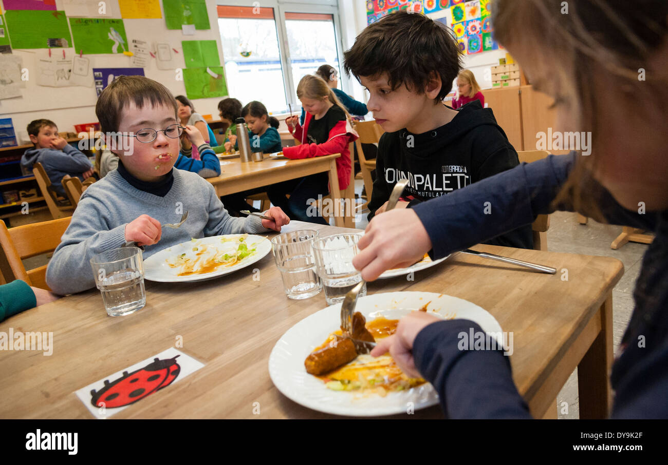 Non-disabled and disabled pupils (in this case a boy suffering from Down's syndrome) have lunch together in their classroom. - Stock Image
