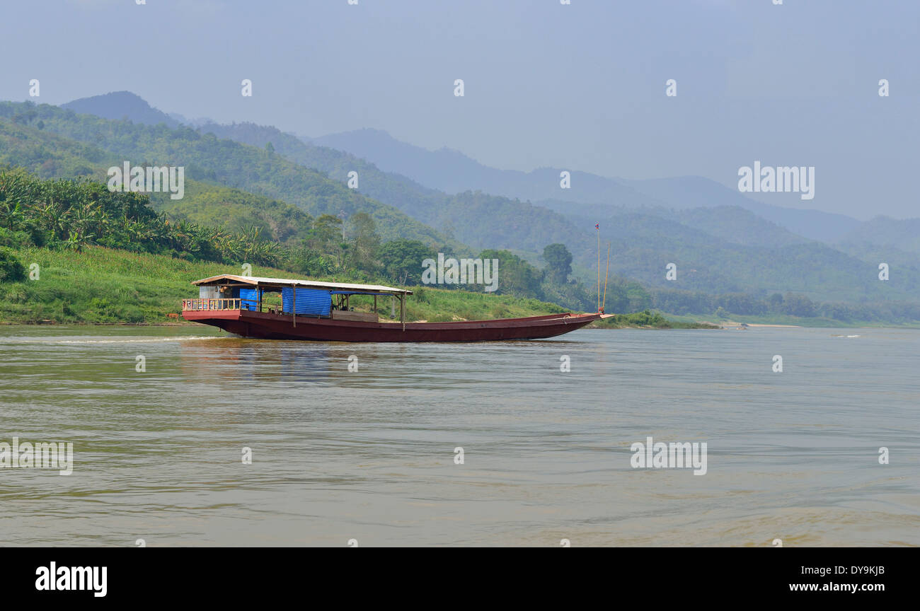 Passenger ferry that plies the river travels the Mekong River through jungle terrain of Laos from Luang Prabang to Chain Khong - Stock Image