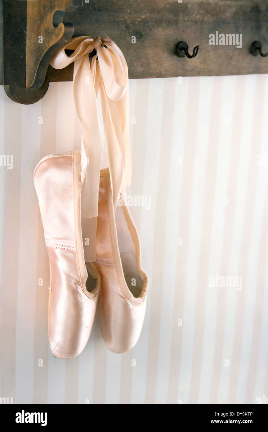 Cream color ballet pointe shoes hanging from wooden rack with striped wallpaper for copy space - Stock Image