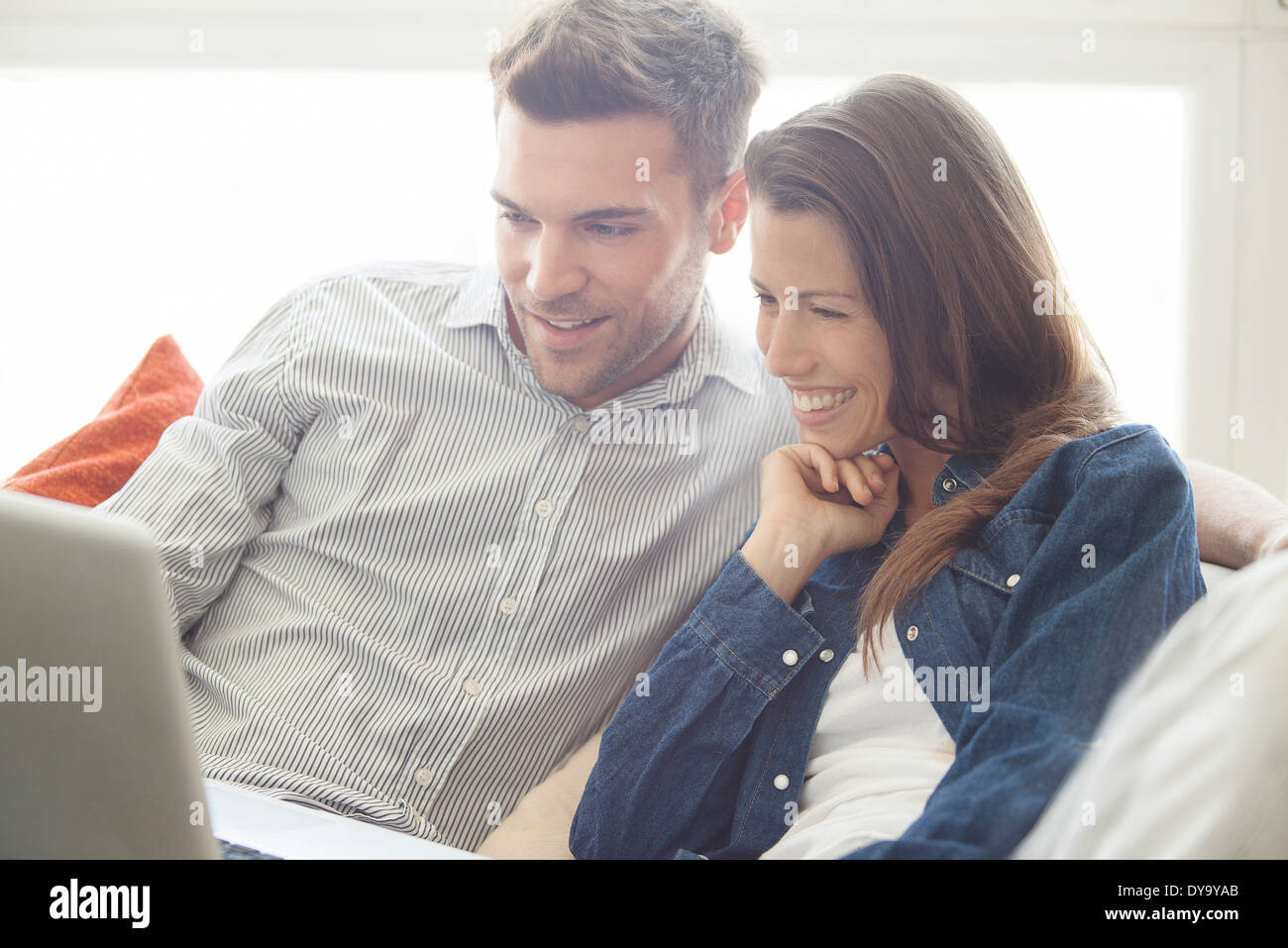 Couple relaxing at home looking at laptop computer together - Stock Image