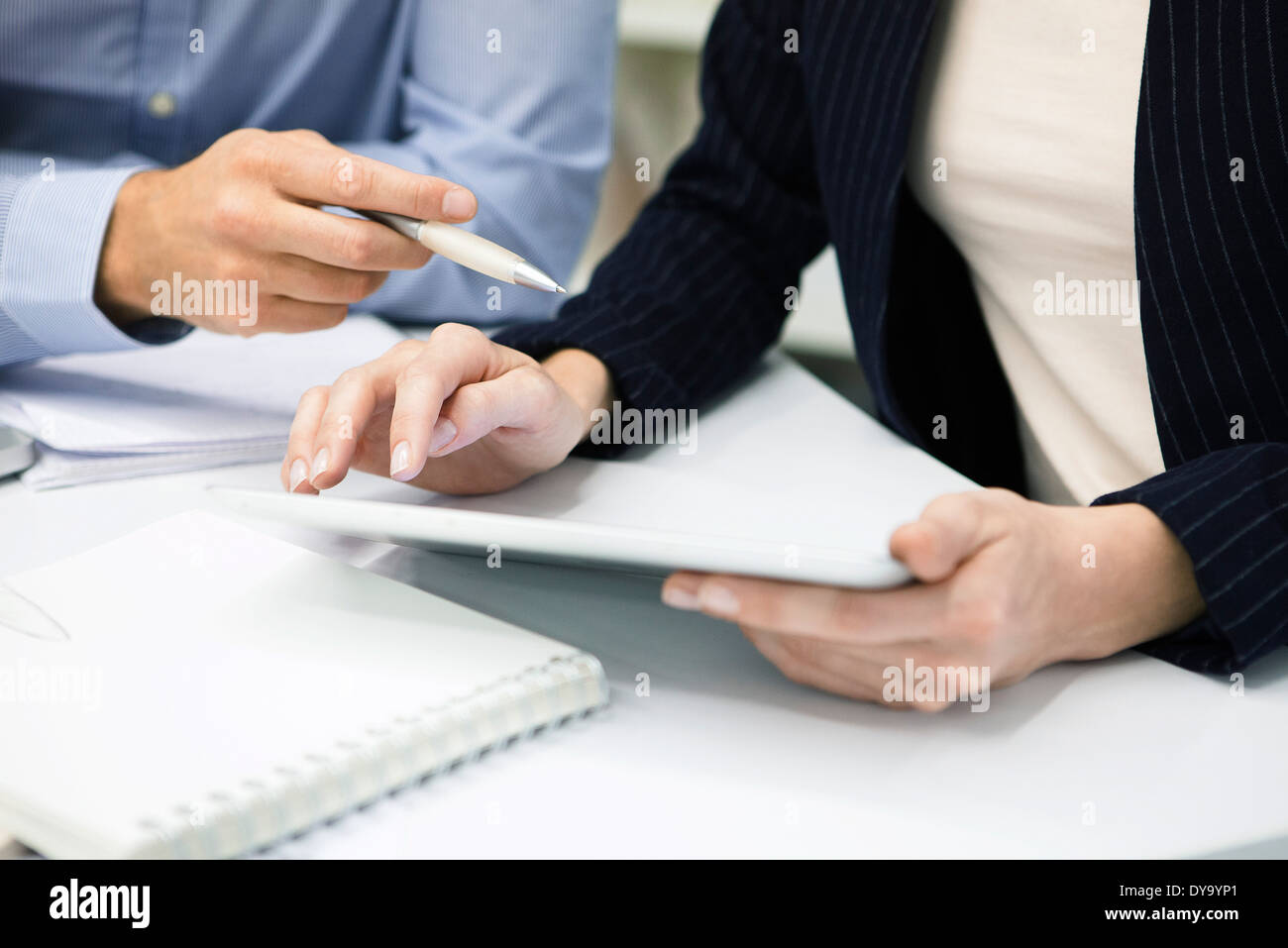 Colleagues using digital tablet, cropped - Stock Image