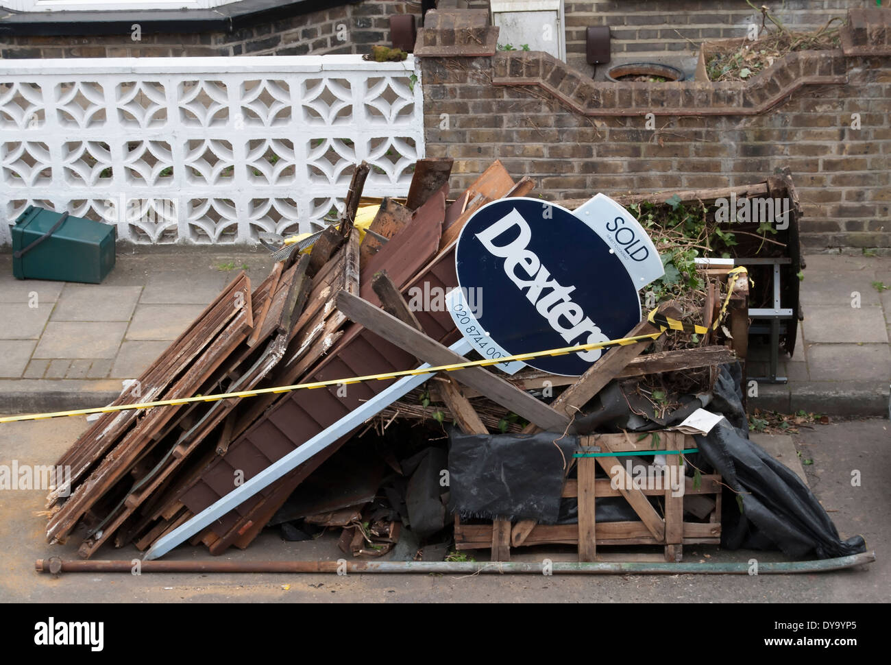 estate agents sold sign with a pile of household rubbish, in twickenham, middlesex, england - Stock Image