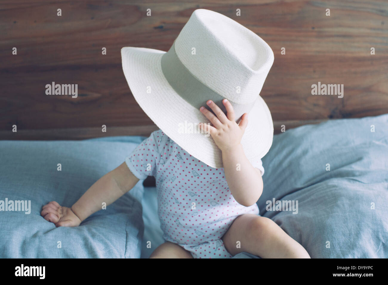 Baby with face obscured by large hat - Stock Image