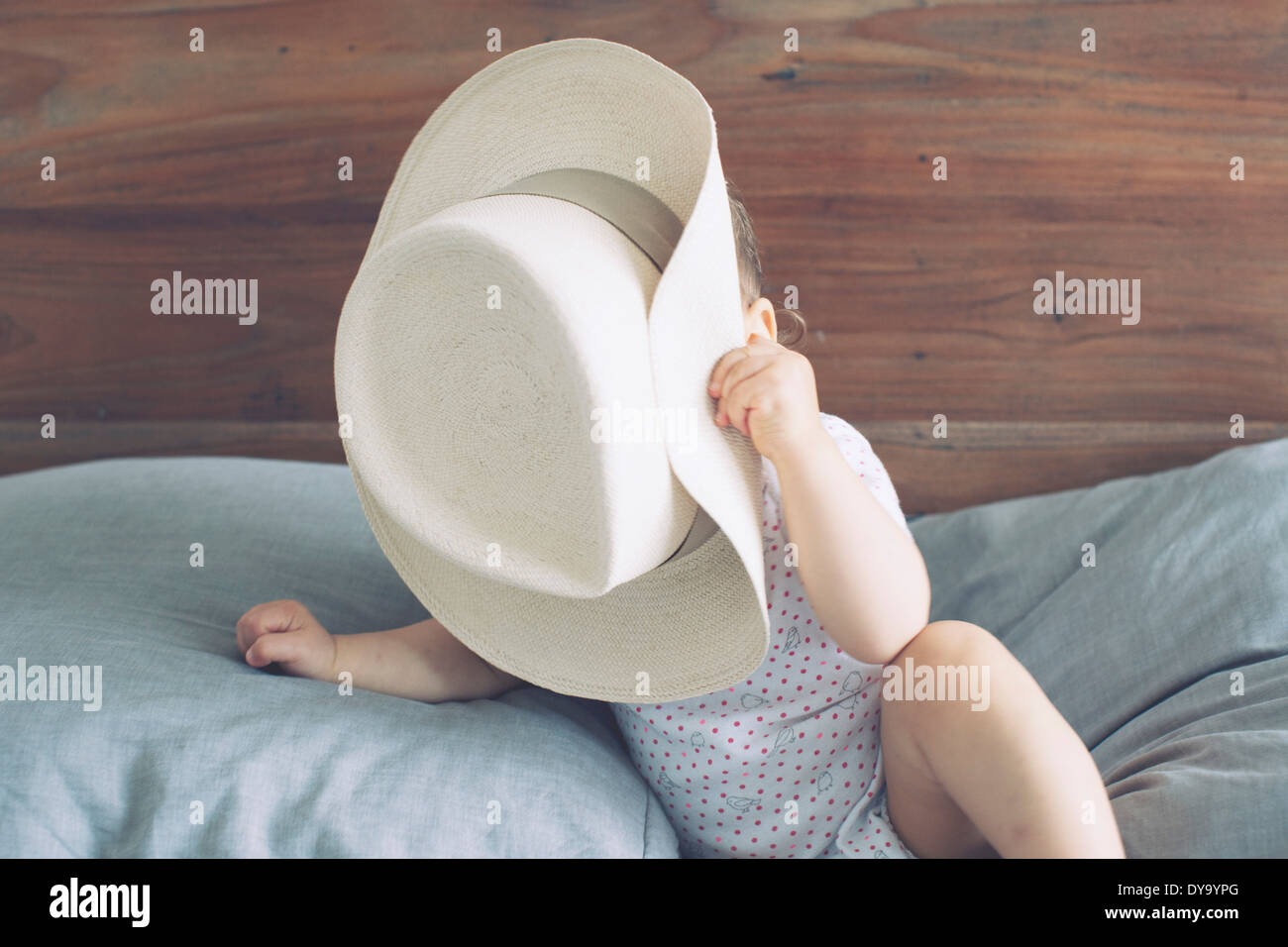 Baby with face obscured by oversized hat - Stock Image